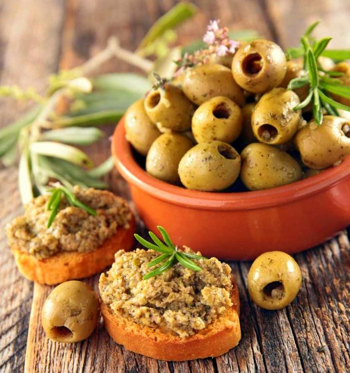 Mama faith's olive tapenade spread on crostinis and bowl of fresh olives